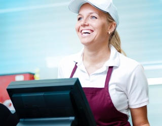 A happy staff member in a quick service restaurant enjoys Cloud Cover Music, a business music solution.